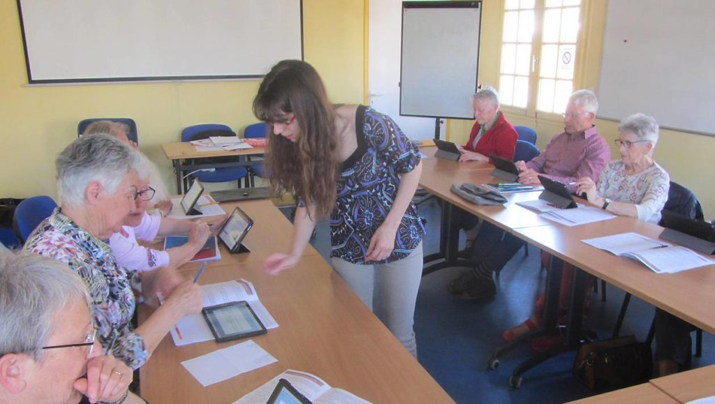Groupe de seniors participant à un atelier mémoire en jeux sur tablette tactile